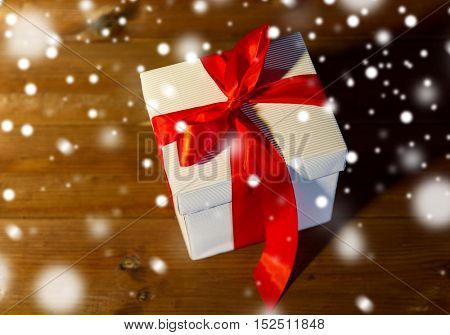christmas, holidays, presents, new year and celebration concept - close up of gift box with red bow on wooden floor from top