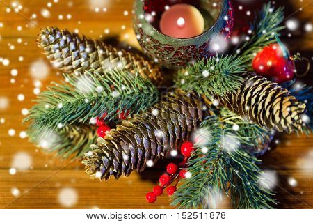 christmas, decoration, holidays and new year concept - close up of natural fir branch decoration and fir-cone and candle in lantern on wooden table