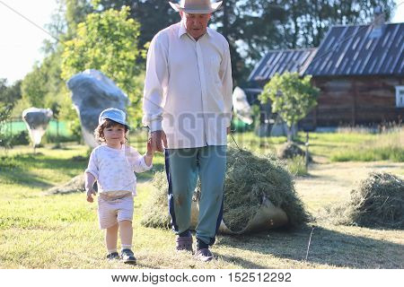 young grandfather bringing up grandchildren on his country area on a summer evening