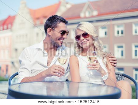 summer holidays and dating concept - smiling couple in sunglasses drinking wine in cafe