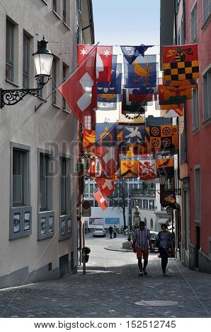 ZURICH, SWITZERLAND - APRIL 15, 2015: Zurich old narrow street with hanging flags of different countries and strolling people. Switzerland.