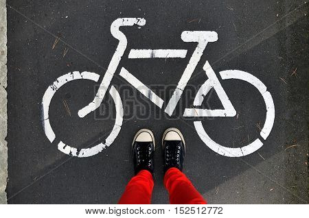 Legs in the red pants and sneakers on the gray asphalt on a background sign of cycle track. Look down.