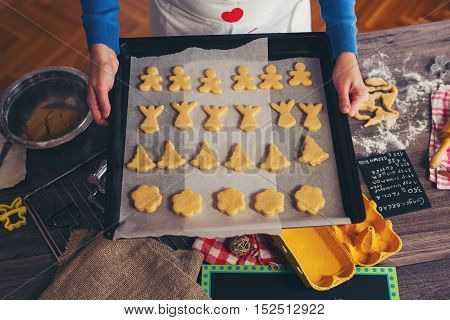 Woman make ginger bread for Christmas in the kitchen