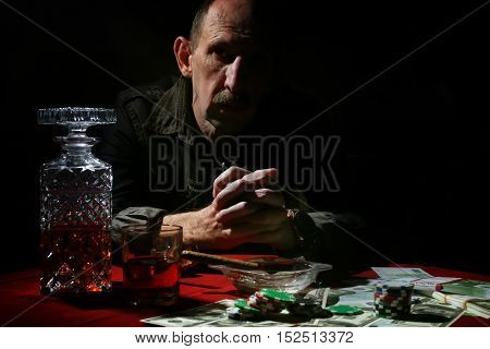 old mustachioed man playing poker at the table