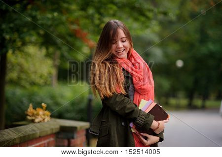 Charming student in a beautiful autumn park. Bright red scarf attracts attention. In the hands of a girl holding tutorials. In the background is a bouquet of fallen autumn leaves. Early autumn.