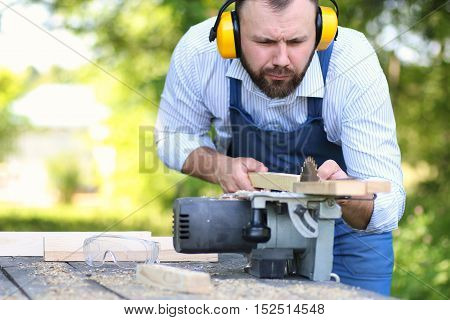 bearded handsome man in working clothes cut on the circular saw