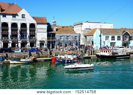 WEYMOUTH, UNITED KINGDOM - JULY 18, 2016 - Fishing boats in the harbour with quayside buildings and pubs to the rear Weymouth Dorset England UK Western Europe, July 18, 2016.