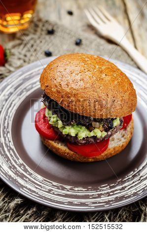 black bean burger with mashed avocado caramelized onions and tomatoes
