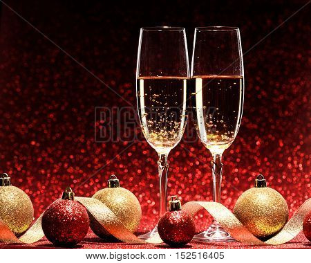 two glasses of champagne ready for christmas celebration, on red background