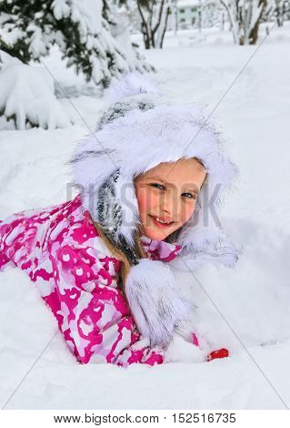 Portrait of little girl in winter clothes and warm hat with deep snow under fir tree.