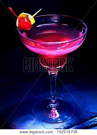Alcohol cocktail with cherry on black background. Cocktail decoration by lemon slice.