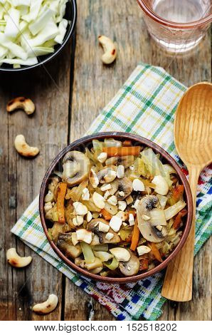 Cashew cabbage with mushrooms on wood background.
