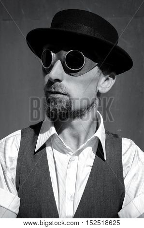 Portrait of a steampunk man in a hat. Black and white photography