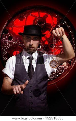 Bearded man in hat holding watch on clock mechanism background. Portrait of a steampunk man