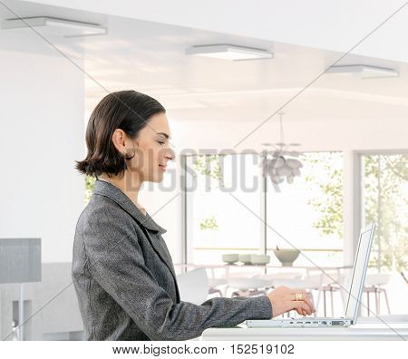 Happy caucasian businesswoman typing on laptop computer a bright home, wearing suit, looking at screen, sitting, small smile.
