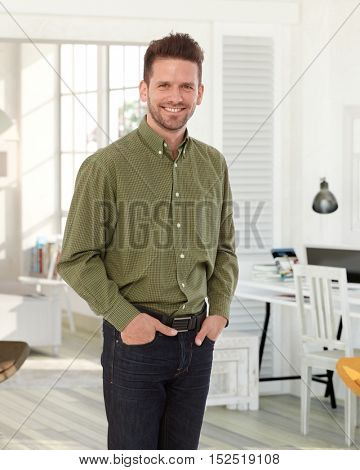 Confident happy young man standing in living room at home, smiling, looking at camera.
