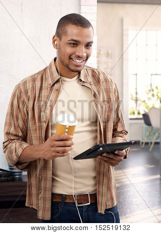 Young black guy listening to music at home, holding tablet and coffee.