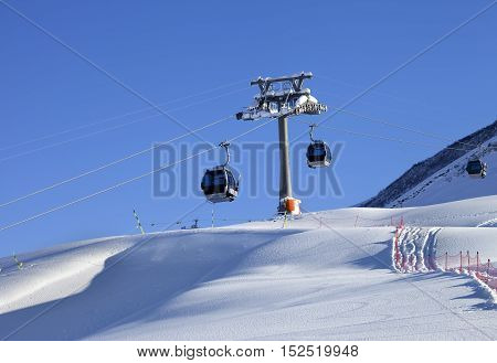 Gondola Lift And Off-piste Slope With New-fallen Snow On Ski Resort At Sun Evening