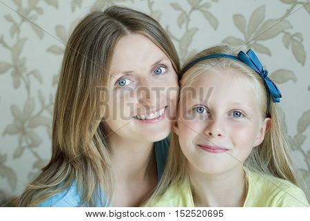 Close-up portrait of mother and her blonde teenage daughter
