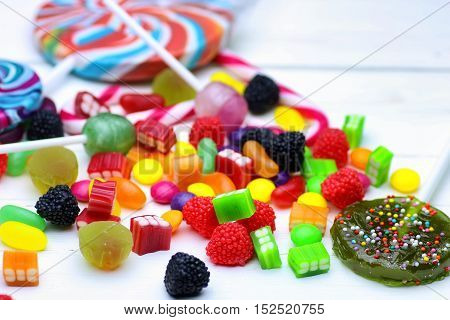 various sweets candy colored jelly beans on a wooden background