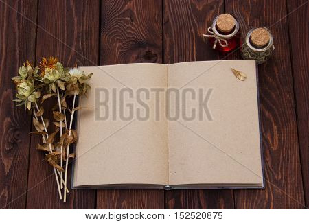 Open book with blank pages and dried herbs. Notepad with pages of kraft paper. Autumn dry flowers
