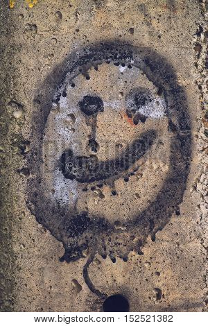 Generic smiley face emoticon graffiti on concrete wall
