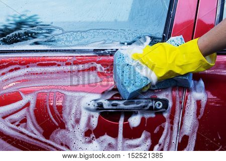 a red car is washing in soap suds
