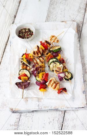 Top view of chicken skewers or shashlik with grilled vegetables (mushrooms paprika salad zucchini onion)