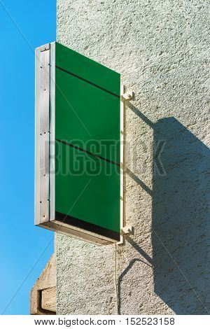 Retail store blank green square signboard as copy space mounted on exterior wall