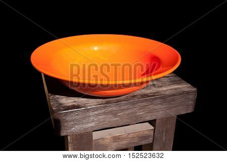 Deep dish orange on brown wooden surface isolated on a black background