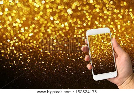 hand holding smart phone taking picture of blurred bokeh lights background