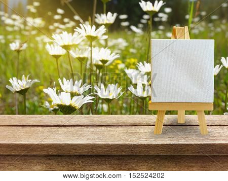 wooden table with nature background with white board and copy space
