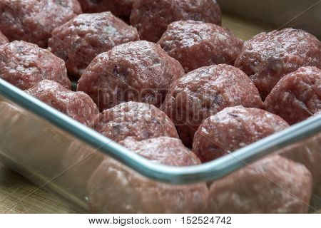 Red raw croquettes in the glass bawl
