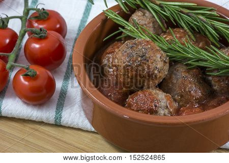 Croquettes with rosemary and cherry on kitchen towel in clay bowl