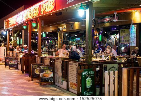 CYPRUS, PROTARAS, FOOLS AND HORSES PUB - OCTOBER 11, 2016: People sitting in the street pub at night