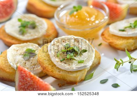 Baked spicy crostini appetizers with goat cheese and fresh herbs served on a white serving plate with fig honey and fresh figs