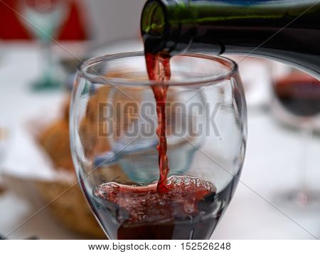 Pouring red wine into the glass in a festive meal in a restaurant