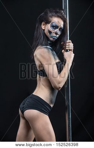 Hot pole dancer in black sport underwear holds her hands on the pylon in the studio on the dark background. She has a body-art on her body. Girl looks into the camera with a grimace. Vertical.