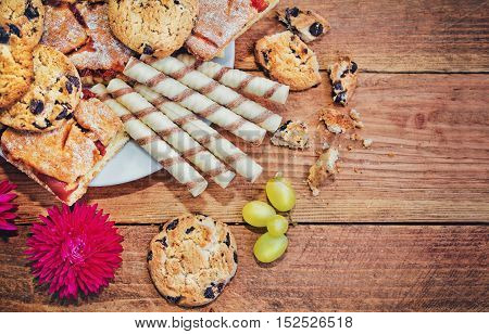 variety of sweet pastry - homemade jam pie, cream rolls and cookies with chocolate on a plate