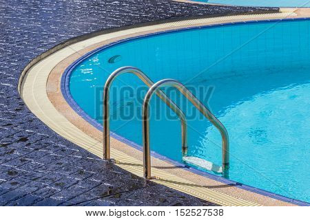 The steel ladder and clear blue swimming pool.