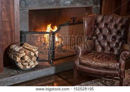 Leather armchair in retro style near the fireplace