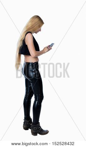 back view of standing young beautiful  girl with tablet computer in the hands of. girl  watching. backside view of person.  Isolated over white background. Blonde in leather trousers looks at phone.