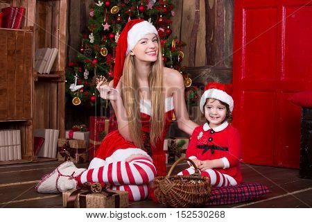 Cute girls sitting with presents near Christmas tree in Santa costumes, smiling and having fun. Xmas atmosphere at home. New year eve.