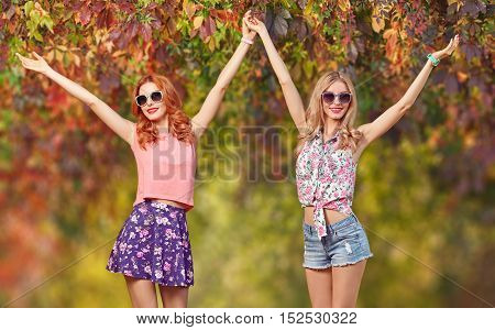 Sisters Friends Crazy Enjoy Autumn Nature. Fall Fashion. Urban Model Woman in Fashion Outfit Having Fun. Autumn Outdoor Park. Glamour Sexy Hipster Girl, fashion Trendy Hairstyle, Stylish Sunglasses.