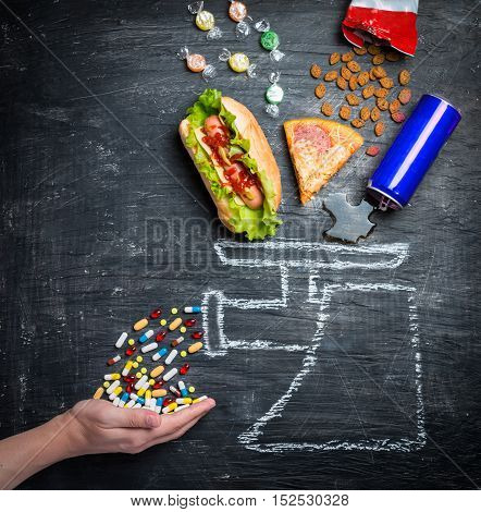 fast food and medicines on a black background. The concept of healthy food.