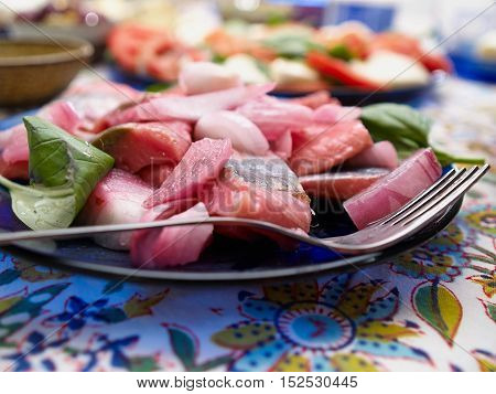 Close up of tasty sliced fresh herring fillets served with basil