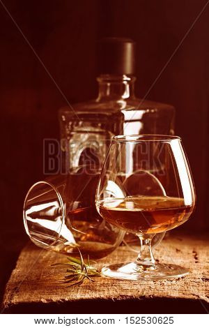 Glass of brandy or cognac and bottle on old oak wooden table. Dark photo.