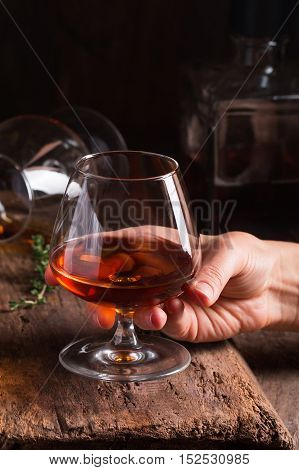 Glass of brandy or cognac in a hand on old oak wooden table. Dark photo.