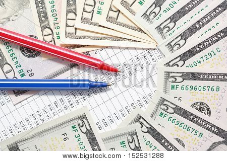 Red and blue pens near money on paper background with digits