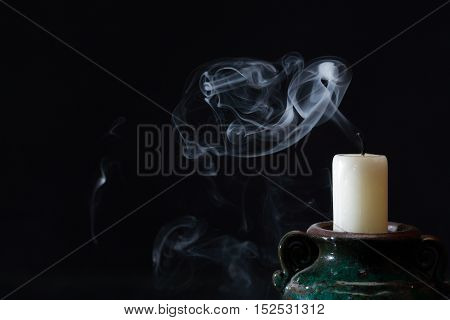 One extinguished candle with smoke on dark background